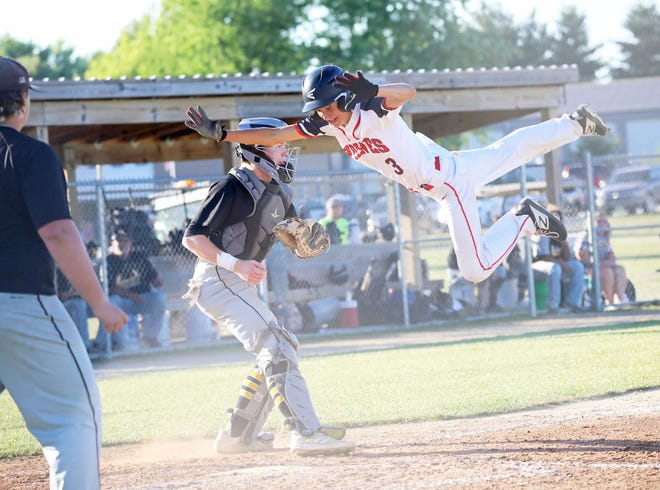 Winfield-Mt. Union sophomore Jacob Haines attempts to leap past New London catcher Tucker Gibbar at home plate in their game at New London Wednesday night.
