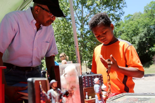 Terry Strothers talks with Dimitri Donald, 11, of Burlington, June 24, 2017, while he holds a pair of shackles at a display table, during the 20th annual Juneteenth event, at DeEdwin and Gladys White Memorial Park in Burlington. The celebration commemorates June 19, 1865, when the last slaves were freed in Galveston, Texas.