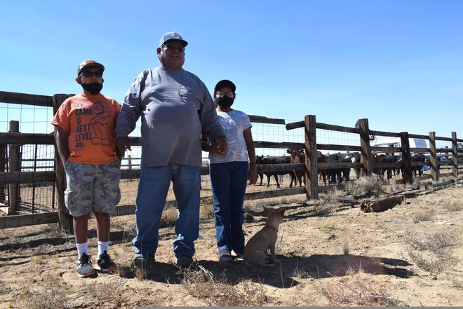 In this Oct 1, 2020 image, Navajo rancher Timothy Largo and his grandchildren pose for a photograph outside a corral at the Sims Ranch near Crownpoint, New Mexico.
