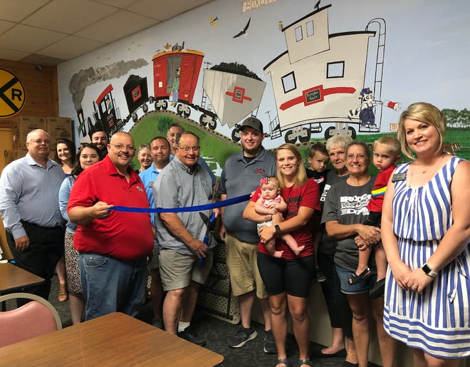 Members of the Lieber family, employees and other officials pose for a photo during a ribbon cutting event Monday to signify the 40th anniversary of Lieber's Boxcar Express, 1974 N. Henderson St.
