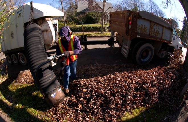 John Floyd controls the vacuum tube that sucks up the leaves piled along Bloomington's city streets in the fall of 2004. Leaf collection has been a citywide program each fall for many years.