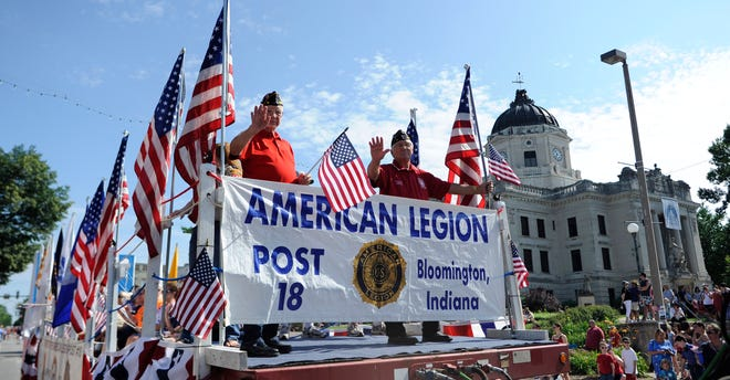 Members of the American Legion Post 18 wave to the crowd during the 2018 Fourth of July parade in downtown Bloomington. This year, a reverse parade is planned in Indiana University's Memorial Stadium parking lot.