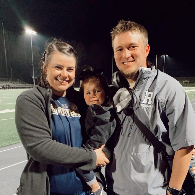 T.C. Roberson track and field coach Colton Brackett, the 3-A West Regional meet director, poses with his wife, Lindsey, and their daughter, Averi recently at Roberson.