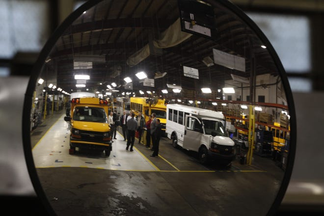 Visitors to the Collins Bus Corporation plant are seen reflected in a mirror along a bus production line during a tour of the plant in this file photo. The small school bus manufacturing plant has temporarily shut down due to the global shortage of semi-conductor chips.