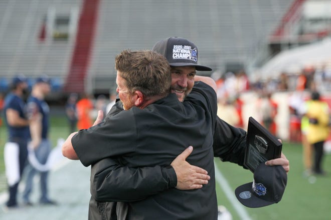 Hutchinson Blue Dragons head football coach Drew Dallas embraces special teams coordinator Andrew Krause following the Blue Dragons' NJCAA national championship victory over Snow College 29-27 at War Memorial Stadium in Little Rock, Ark.