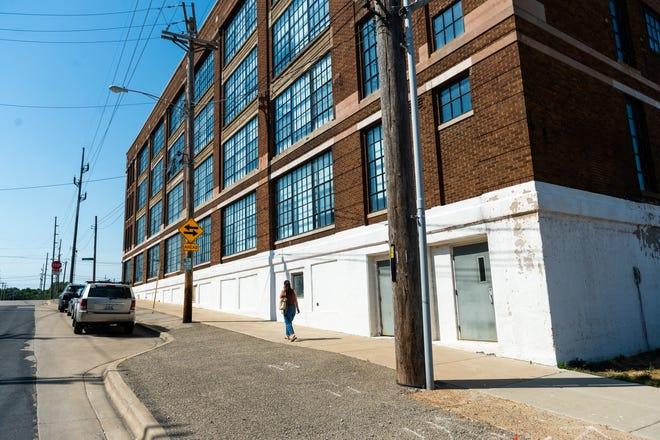 A pedestrian walks past the Persimmon Lofts on Thursday, June 17, 2021.