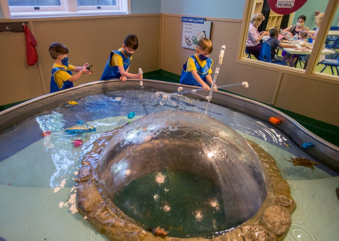 The Schwarzentraub brothers, left to right, Kairos, 3, Rhyse, 7, and Zion, 5, play together in the water feature while another group works on a craft project in the room next door at the Peoria PlayHouse Children's Museum in Glen Oak Park. The PlayHouse is planning to reopen gradually and currently requires all visitors over the age of 2 to wear a mask.