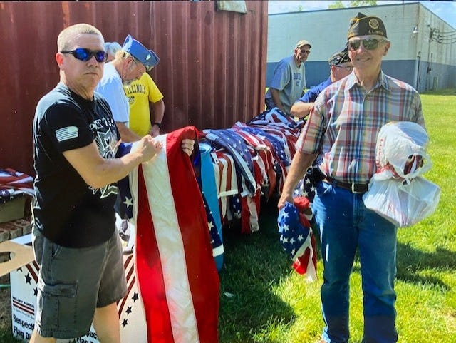 Preparing flags for their proper disposal are a veteran helper on the left and Lyle Johnson, right.