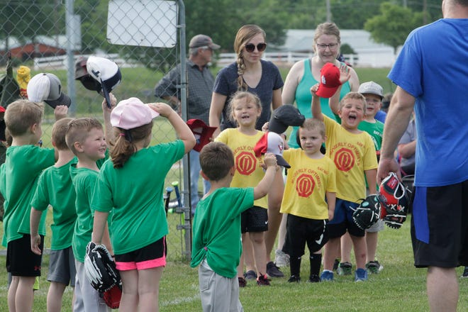 Players with the Huntsville Hawks (green shirts) and Higbee Tigers age 4-5 year old teams of the Moberly Optimist Club T-ball League salute one another following a league game played this summer at the Howard Hils Athletic Complex.