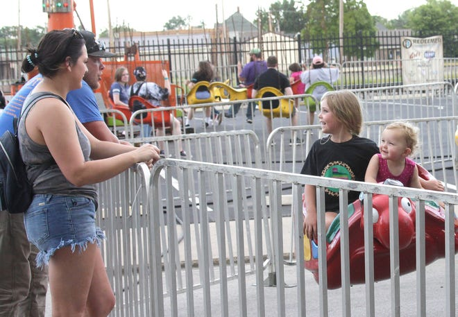 Five year-old Quinn Day holds onto her 2-year old sister Brenna as they enjoy their children's amusement ride going past their parents, Jake Day and Kate Lewis, Wednesday evening at the Railroad Days festival in downtown Moberly. The four-day event offers a variety of evening activity and culminates Saturday, June 19.