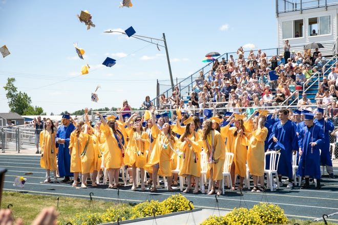 Mortar boards are flung into the air as Ida High School graduates celebrate.