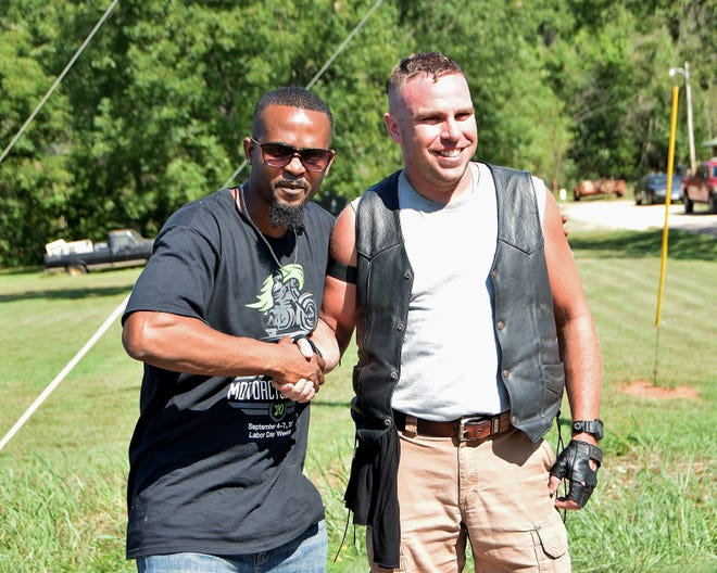 Tour organizer Derrick Smith Jr., left, congratulates rider Eric Miksch at the completion of a Black Towns Motorcycle Tour.