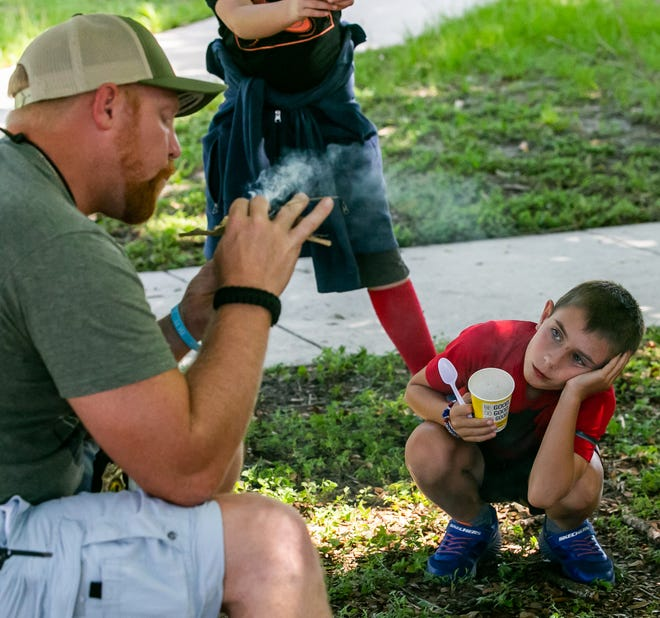 In this photo from June 8, camper Ryan Silad, 8, watches as Survival Trainer Steven Clayton of North Florida Survival blows on the embers to create fire. About 20 summer campers took part in the week-long Outdoor Explorers at the Discovery Center Summer Camp. With school out and monthly child tax credits available from the IRS in July, some families are considering using the money for camps and child care during the day while they work.