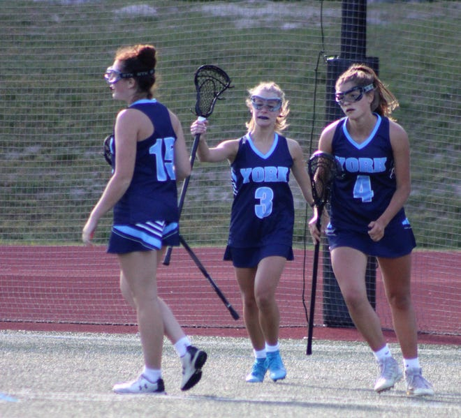 York's Ashley LaPierre (15), Carly Mitchell (3) and Clara Pavuk (4) celebrate after Mitchell scored a goal in the first half of York's 19-8 Class B girls lacrosse semifinal loss to Yarmouth on Wednesday.