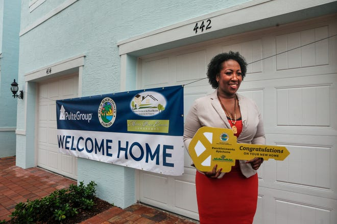 Bernita Banks, the first homeowner in the Merry Place Estates development, poses for photos after the City of West Palm Beach unveiled 36 homes built under its workforce housing program in the Pleasant City neighborhood, on June 17, 2021.