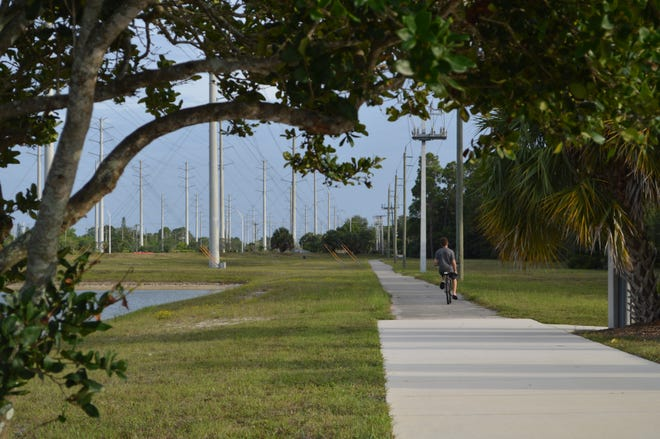 A bicyclist in Royal Palm Beach headed toward Okeechobee Boulevard travels on a makeshift extension of a La Mancha Avenue pathway. The village estimates a permanent extension would cost $3 million and unsuccessfully sought $450,000 for the project through this year's state budget.