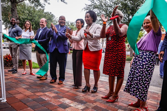 Bernita Banks, the first homeowner in the Merry Place Estates development, smiles Thursday as the city of West Palm Beach unveils 36 houses built under its workforce housing program in the Pleasant City neighborhood.