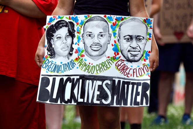 A poster at a racial justice rally in June 2020 features the names and faces of three black Americans killed by police.