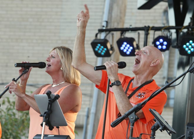 Lise' Berquist (left) joins LaFlavour lead singer Craig DeBock on stage Thursday evening to kick off Massillon's 2021 Summer Concert Series. The show with LaFlavour was the first live performance at the city's downtown Duncan Plaza since renovations were completed.