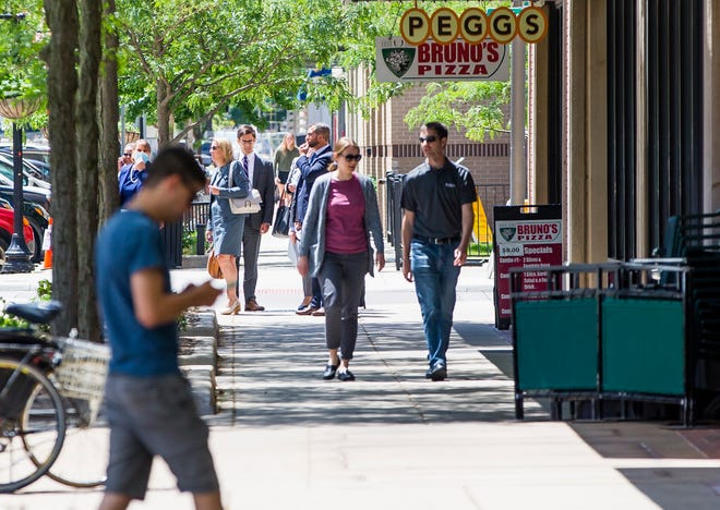 People make their way along Michigan Street in downtown South Bend on Wednesday during the lunch hour. Businesses say foot traffic has returned to normal in recent weeks.