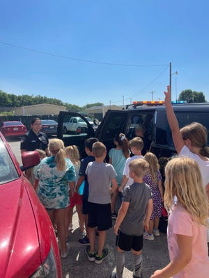 Stephenville Police Officer Maureena Salazar answers questions for youngsters while giving them a tour of her patrol vehicle during a Stephenville Parks and Rec summer camp event on Thursday.