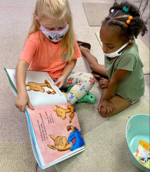 First graders in a summer school program in North Carolina wear masks and look at book.