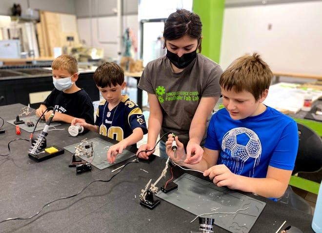 SSC student instructor Natalie Carrion helps children learn how  to solder electronic components at the Faulhaber Fab Lab.
