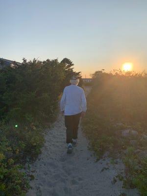 Lauren Daley's father,  , walks up a beach path at Westport Harbor.