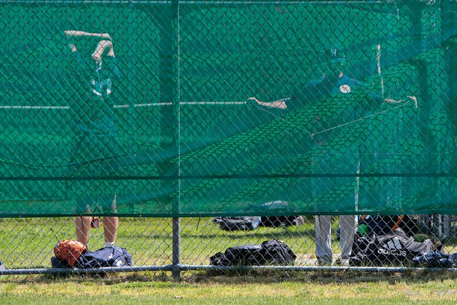 Wareham Gatemen pitchers warm up behind a green fence during their first practice session in preparation for the upcoming Cape Cod Baseball League season.