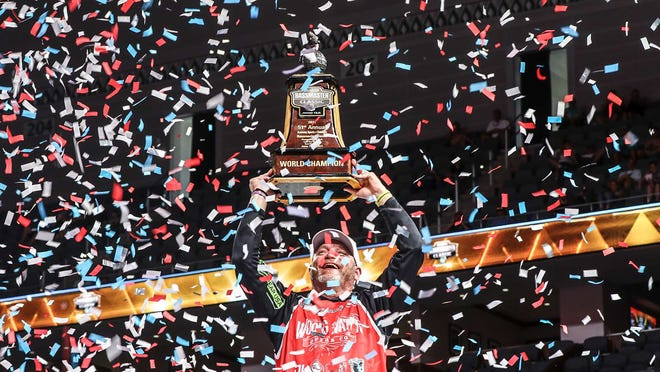 Hank Cherry, of Lincolnton, N.C., hoists the Bassmaster Classic championship trophy for the second straight year June 13 at Lake Ray Roberts in Fort Worth, Texas.
