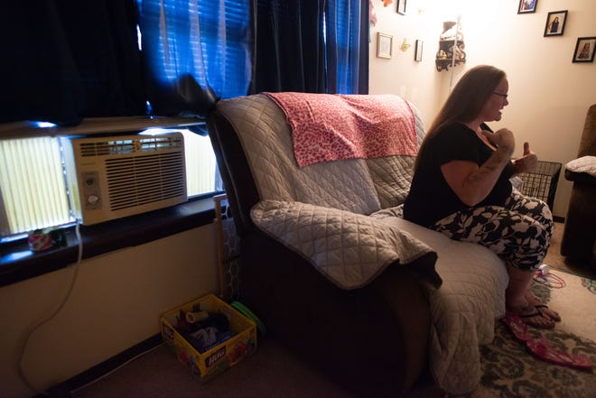 A small window air-conditioning unit keeps the living room of KristiMichaud's apartment somewhat cool, with the help of several fans Wednesday. The unit was given to Michaud by another tenant in her apartment building after she discovered June 7 that her central A/C wasn't working.