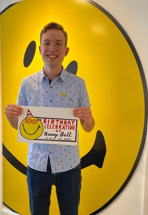 Liam Monahan with his winning smiley logo.