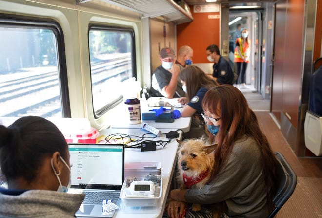 WORCESTER - Kim Eovacious holds her dog Oscar before her vaccination by Karessa Victor on the MBTA's vaccination train, which pulled into Union Station last week.
