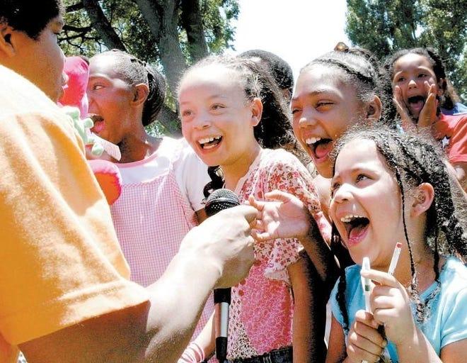 Stefan Creighton (left) leads Jozlyn Jones, Marissa Cade, Janessa Eleazer and Tianna Quinn in a singing contest during the 2005 Juneteenth celebration in Bessemer Park.