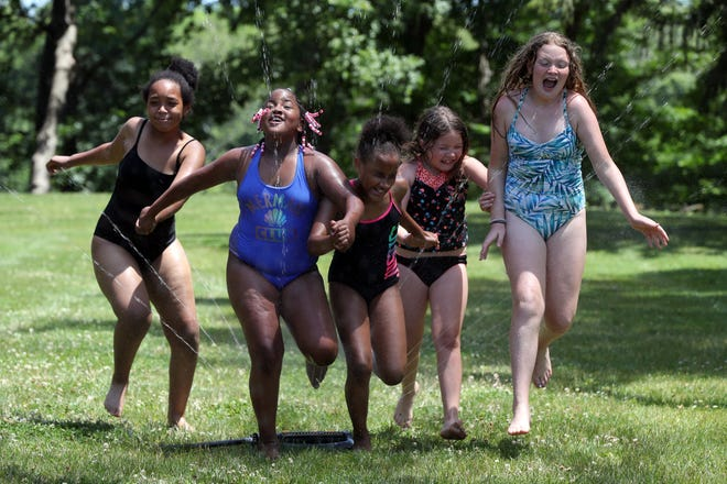 (From left) Zariah Crockett, 11, of Whitehall; Amaya Cousins, 9, of Columbus; Alexandria Fullum, 11, of Columbus; Charlotte Blankenship, 7, of Obetz, and Maggie Carpenter, 10, of Columbus hold hands as they charge through a water sprinkler during summer day camp at the Whitehall Community Park YMCA on June 16.