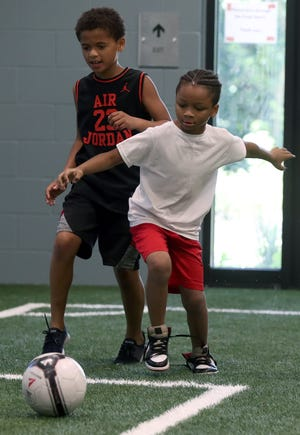 James Harris (left), 10, and Kaden Young, 7, both of Columbus, battle for possession during a soccer game at Whitehall Community Park YMCA's summer day camp June 16.