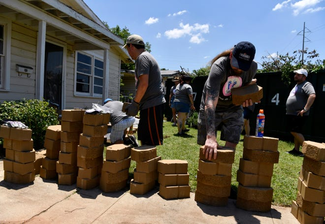 Volunteers lay out flower beds using concrete bricks as its borders Thursday at the Let Us Breathe House at 541 Cockerell Dr. The house was donated to Let Us Breathe, a local community group organized in 2020, and will serve as a center for the group.