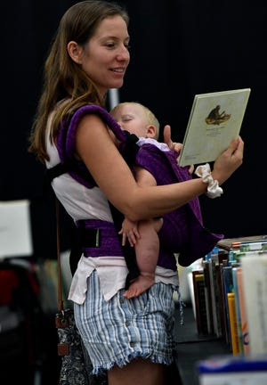 Ashley Hurley picks out a book as her daughter Iris continues to nap during Thursday's Friends of the Library book sale. Volunteers of the sale were allowed to shop early . The sale opens to the general public Friday.