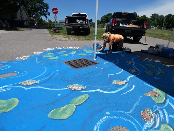 Kymberlee Wood adds detail to a mural surrounding a storm drain in Aumiller Park on Wednesday.