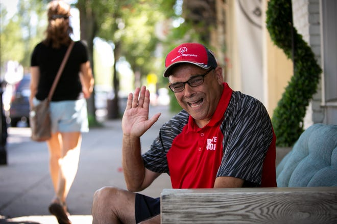 """Johnny Vilardo, a Special Olympian who lives in Milford, smiles and waves as he sits along Main Street, on Thursday, June 17. Vilardo received a gold medal for golf in the 2014 Special Olympics. He also won a silver medal in 18 hole golf in 2018. Vilardo also works at the Milford Kroger and is known around town as """"the unofficial mayor of Milford."""""""