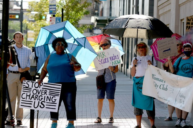 People gather for a rally outside of the Todd B. Portune Center for County Government building Thursday, June 17, 2021 to address sewer rates in Hamilton County.  Communities United For Action and their allies announced the launch of a Fair Sewer Rates Coalition to ensure affordable sewer rates.