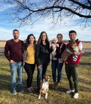 Jen Moseley (center) stands with her children and their spouses. From left, Scott Kornberg, Madie Kornberg, Jen Moseley, Maria Moreno, and Paxton Moreno. Moseley's boxer, Dr. Indiana Jones, sits in front of Moseley.