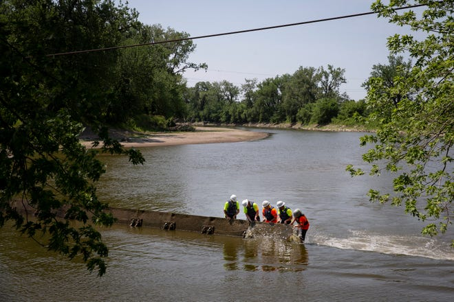 Crews from Synergy Contracting help Des Moines Water Works raise flashboards in the Raccoon River on June 17. The 41 boards serve to back up the river to cover the utility's intake, which pulls 50 million gallons a day to serve customers around the metro.