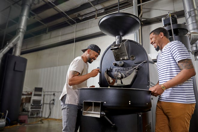 Pernell Cezar (left) and Rod Johnson, owners of Blk & Bold, with one of their coffee roasters.