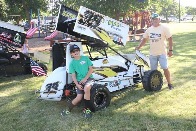 Driver Madden Merrill, 9 years old of Fremont, sits with his micro sprint car, along with his dad Matt.