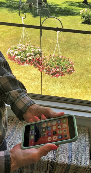 Faye holds her phone in sunporch of her Oconto home. Last year, she fell victim to a scammer who called, posing as her son-in-law.