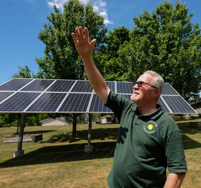 Steve Potter shows how the direction of the sun moves and strikes the solar array in his backyard Thursday, June 17, 2021.