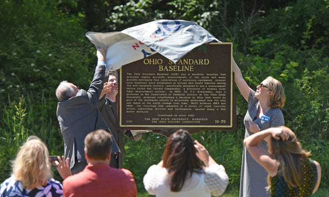 Dorey Diab, President of North Central State College, Norman Jones, Dean & Director and Professor of English at Ohio State University Mansfield and Krista Horrocks of the Ohio History Connection unveil the plaque commemorating the Ohio Standard Baseline.