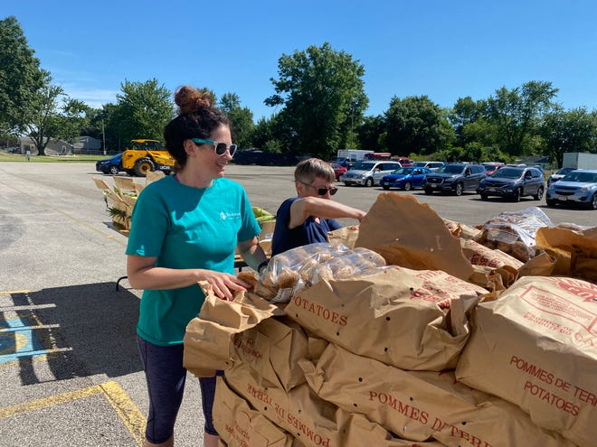 Buckeye Community School English teacher Angie Lowe and Marion City School substitute cook Sharon Leonard open a bag of potatoes during the community produce market Wednesday, June 16, 2021. The market is a partnership between BCS, MCS and the Mid-Ohio Food Collective.