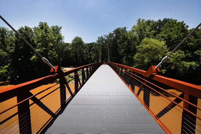 A 270-foot long steel suspension bridge over the Wolf River is one of the largest undertakings in the Greenway expansion project, seen here nearly completed on Thursday, June 17, 2021.